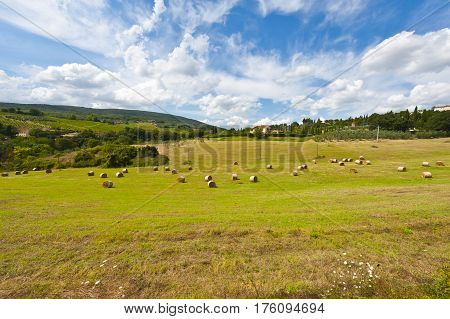 Tuscany Landscape with Many Hay Bales on the Background of the Italian Village