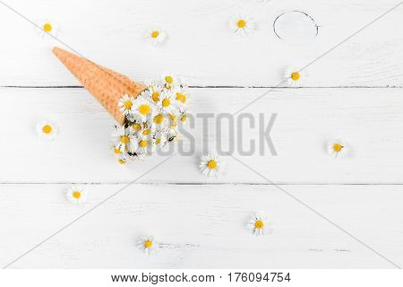 daisy flowers in the ice cream cone on white wooden background flat lay top view
