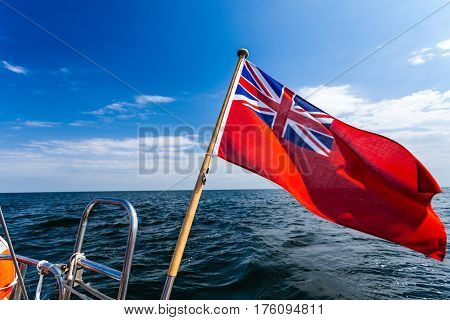 The uk red ensign the british maritime flag flown from yacht sail boat blue sky and baltic sea. Summer and travel voyage