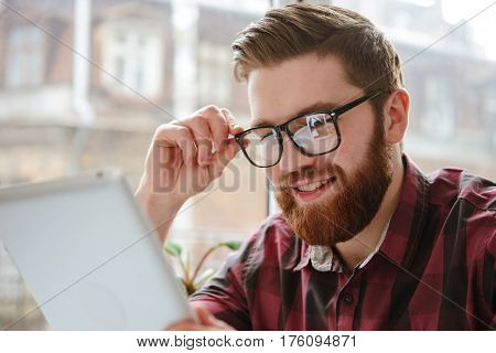 Image of smiling bearded young student man wearing glasses sitting in cafe while using tablet computer. Looking aside.