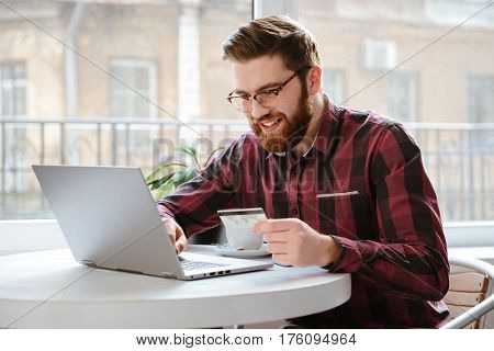 Photo of smiling bearded young man sitting in cafe while using laptop computer and holding debit card. Looking at laptop.