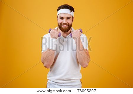 Happy sportsman which doing exercise with lightweight dumbbells and looking at camera. Isolated orange background