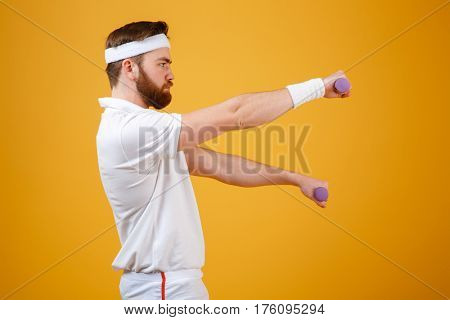 Side view of sportsman which doing exercise with lightweight dumbbells. Isolated orange background