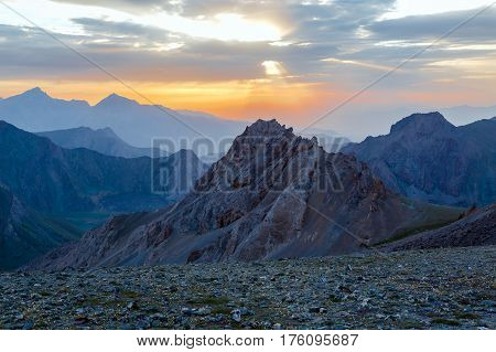 Sunset mountain panorama Silhouettes of highland ridges and peaks of warm and cool tones visible perspective distance luminous Sunset on background