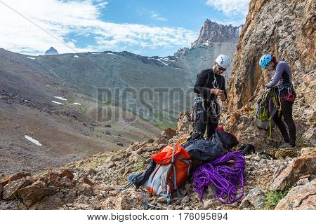 Team of two athletes male and female placing gear packing backpacks staying on rocky terrain at beginning of Climbing Route on Mountains blue Sky and Peaks on Background.