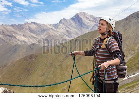 Female Mountain Climber holding Rope belays her climbing partner wearer in protection helmet safety harness highland landscape on Background