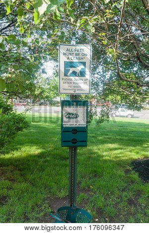 Secaucus New Jersey USA - May 10 2012: Dogs must kept on a leash no dog fouling and an empty Baggit waste bag dispensor and bin sign advising pet owners to clean up after their pets to prevent the spread of diseases and parasites