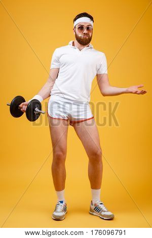 Vertical image of Displeased sportsman in sunglasses and with cigarette in mouth which holding dumbbell and looking at camera