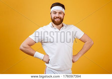 Happy sportsman which posing in studio with arms at hip and looking at camera. Isolated orange background