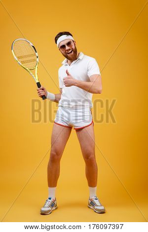 Vertical image of happy sportsman with tennis racquet in hand which showing thumb up and looking at camera. Isolated orange background