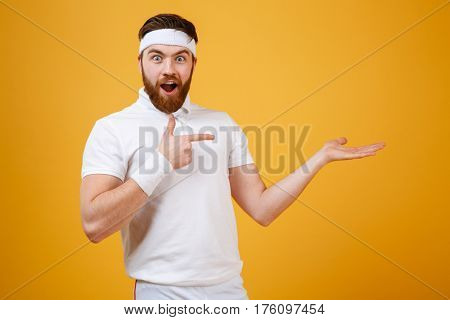 Surprised sportsman which pointing at the invisible copyspace on the pound and looking at camera. Isolated orange background