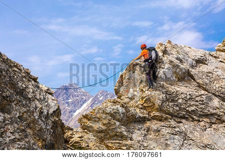 Mountain Climber moving along sharp rocky Ridge using belaying Rope and safety Gear