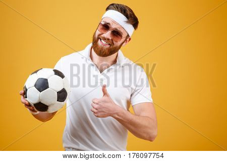 Smiling sportsman in sunglasses which holding soccer ball and showing thumb up