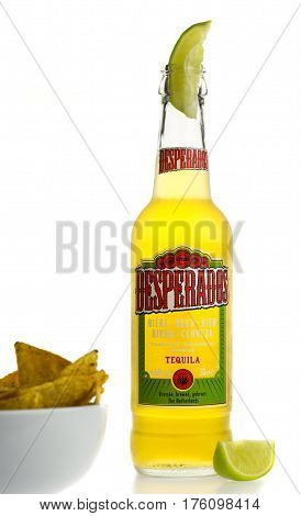 GRONINGEN, NETHERLANDS - MARCH 04, 2017: Bottle of Mexican Desperados Tequila beer with lime wedge and nachos isolated on a white background