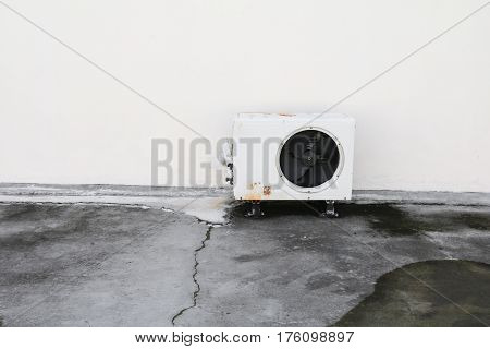old white air conditioner compressor. rust metal on floor