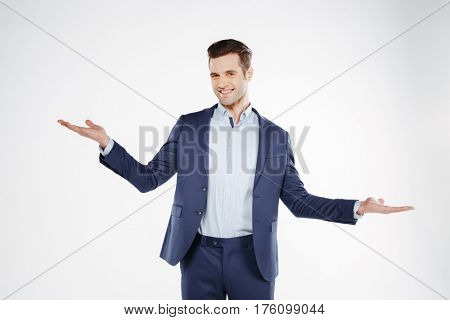 Smiling Incomprehensible business man which posing in studio and looking at camera. Isolated white background