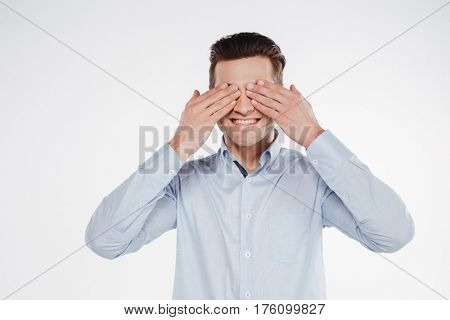 Smiling business man which covering his eyes of both hands. Isolated white background