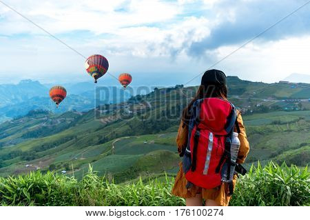 Hiker woman feeling victorious facing and seeing balloon on the mountain Thailand