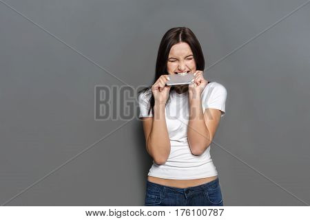 Furious woman bite her phone after hard conversation while standing on gray studio background. Angry girl biting cellphone after unpleasant talk