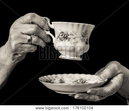 Traditional Teacup And Saucer Held In Elderly Woman's Hands.