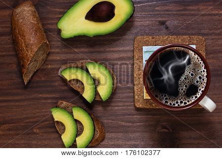 Prepared by myself simple lunch with brown baguette styled bread and avocado and coffee on vintage wooden table