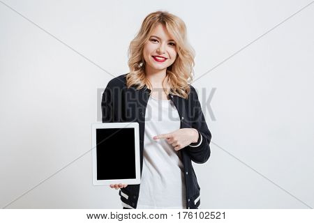 Image of attractive young woman standing over white background showing display of tablet computer to camera and pointing.