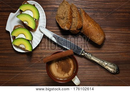Sandwiches with spreading cheese and avocado slices on shell like plate with antique knife and coffee with cinnamon on the oldened wooden table