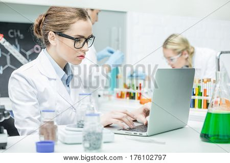 Concentrated female scientist working on laptop in chemical laboratory