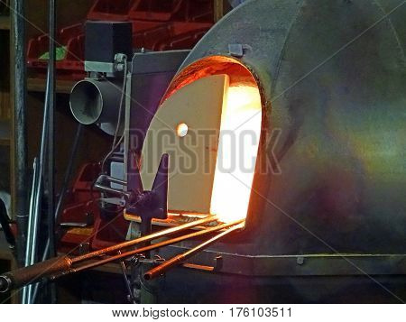 Glass melting furnace in a dark workshop