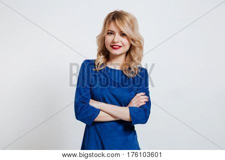 Image of pretty young lady with arms crossed dressed in blue dress standing and posing over white background.