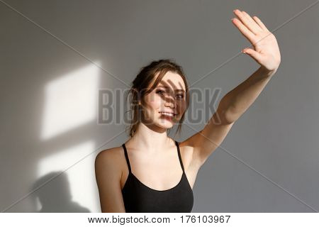Portrait of a young pretty fitness woman standing with outstretched arm, covering from the sunlight