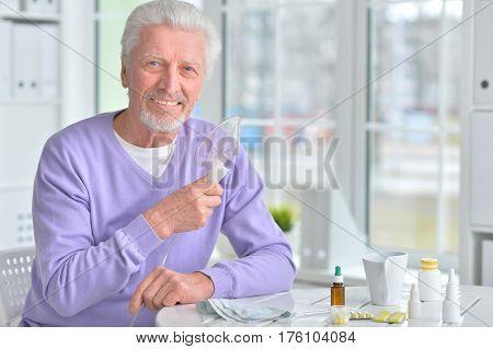 Portrait of an elderly man doing inhalation