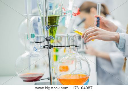Close-up partial view of female scientist working with reagents in chemical laboratory