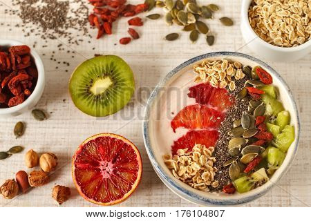Superfoods smoothies bowl with chia seeds, oats, goji berry and fruit. Overhead, top view, flat lay.