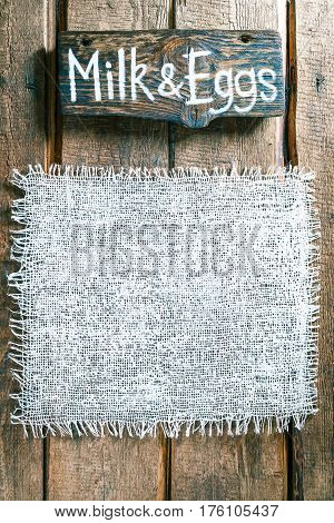 Vertical frame of white burlap on rough pine wood boards. Wooden tablet with text 'Milk and eggs' as title bar. Structured natural style background