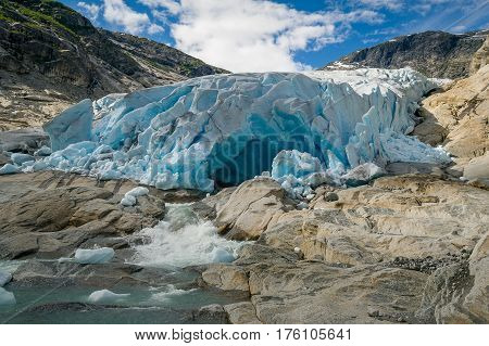 Blue cave from ice and melted water river landscape. Nigardsbreen Glacier, Norway.