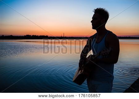 Silhouette of young handsome man playing guitar at seaside at sunrise.