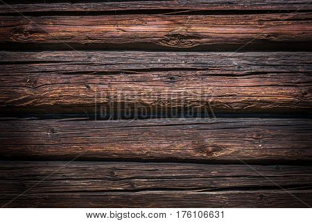 Wooden background. The wall of the old dilapidated logs. Well seen rich texture of the ravaged wood.