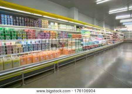 Shelves at supermarket with diary products, blurred bokeh background.