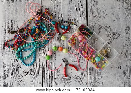 Box With Beads, Plier And Glass Hearts To Create Hand Made Jewelry On Old Wooden Background. Handmad