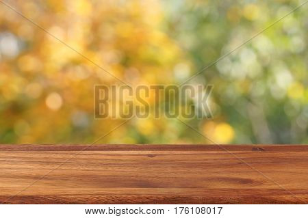 An empty wooden table on a background of autumn trees. The background is blurred. Free place for creativity.