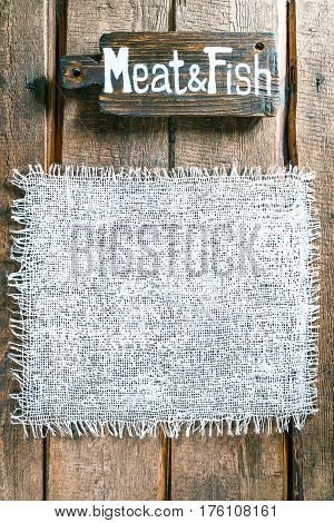 Vertical frame of white burlap on rough pine wood boards. Wooden cutting board with text 'Meat and Fish' as title bar. Structured natural style background