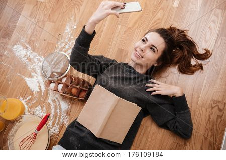 Top view portrait of a smiling pretty woman taking selfie on mobile phone while cooking breakfast and laying on the floor