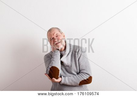 Handsome senior man in gray sweater, having ache in his elbow or neck. Studio shot against white wall.