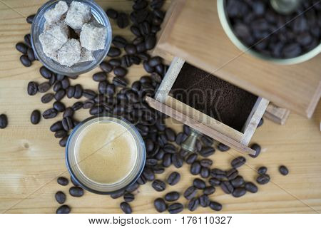 Coffee grinder with espresso and sugar cubes served in small glasses viewed from above with focus to the open drawer with ground beans