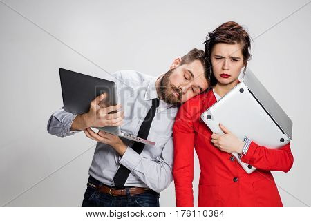 The yawning, bored and sleeping young businessman and businesswoman with laptops on gray background. The concept of relationship of colleagues.