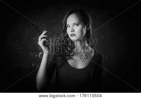 Noir film style woman in long black dress and cigarette in left hand standing back to camera. Female has a long dark hair posing with a gun in her hand. She hides a pistol. Black and white photography. Old fashion photo