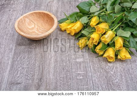 Yellow Roses And A Wooden Bowl On A Wooden Background