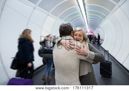 Beautiful senior couple in winter clothes in the hallway of subway in Vienna hugging. Man welcoming his wife.