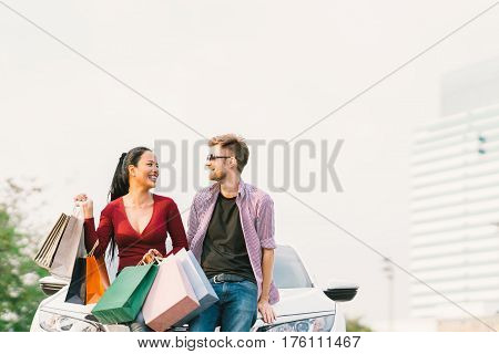 Multiethnic couple with shopping bags smiling and sitting on white car. Love casual lifestyle or shopaholic concept. With copy space